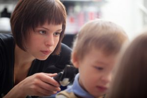 Hairstylist cutting a young boys hair